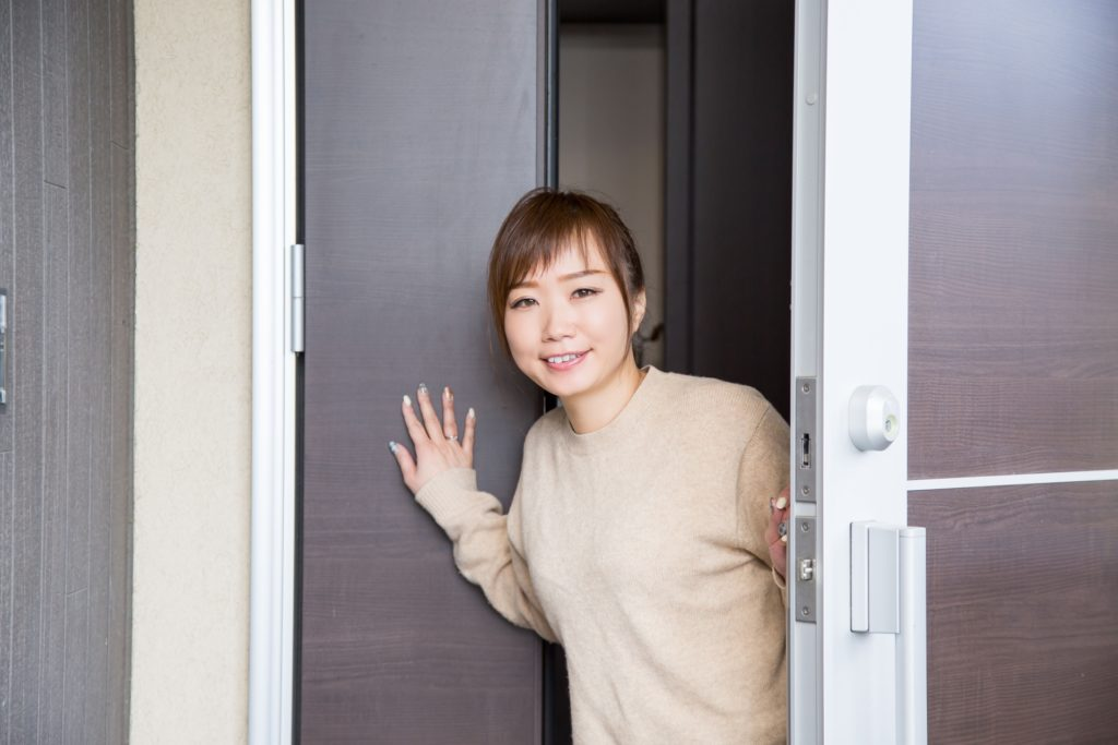玄関で出迎える女性