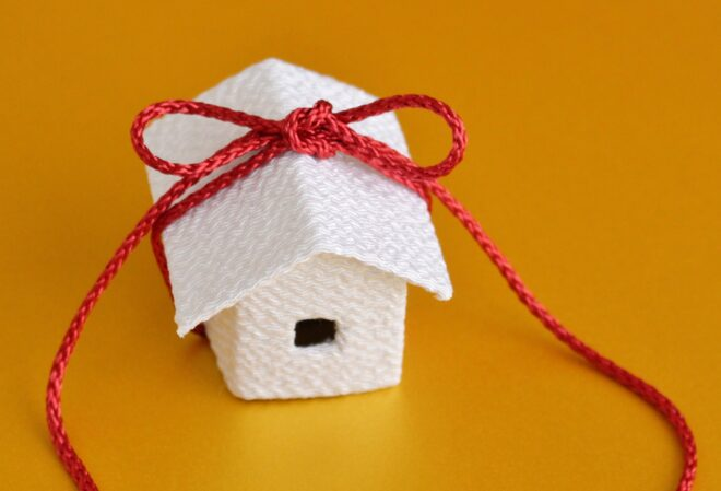 赤いリボンが結ばれた白の家の模型